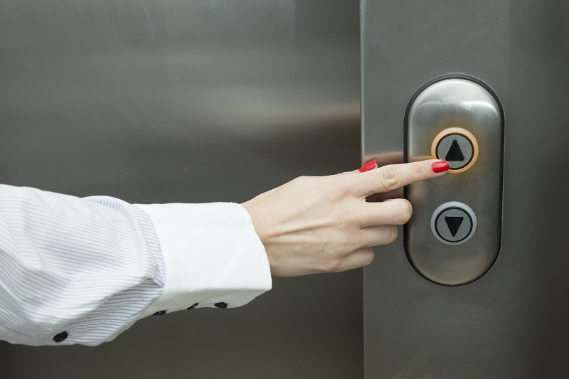 Woman pressing elevator up button
